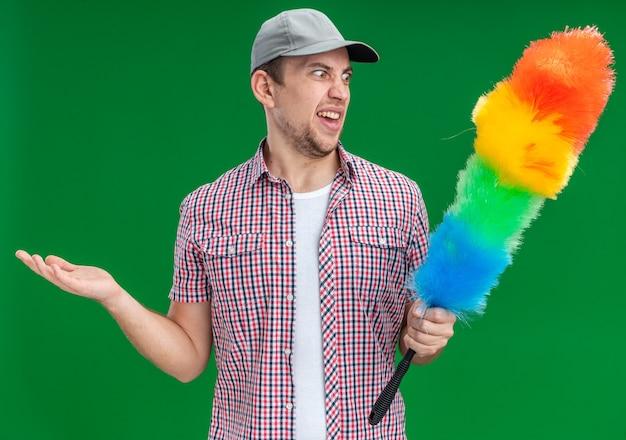 Un giovane ragazzo scontento che indossa un berretto che tiene e guarda il pipidaster che spande le mani isolate su sfondo verde