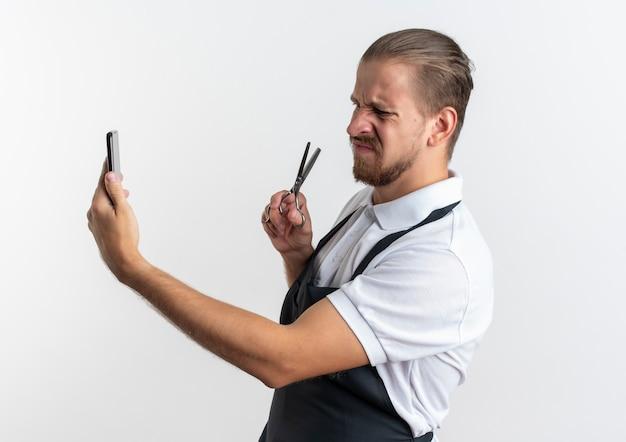 Недовольный молодой красивый парикмахер в униформе, держащийся и смотрящий на мобильный телефон с ножницами в руке, изолированном на белом фоне