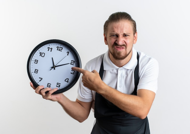 Unpleased young handsome barber wearing uniform holding and pointing at clock isolated on white background