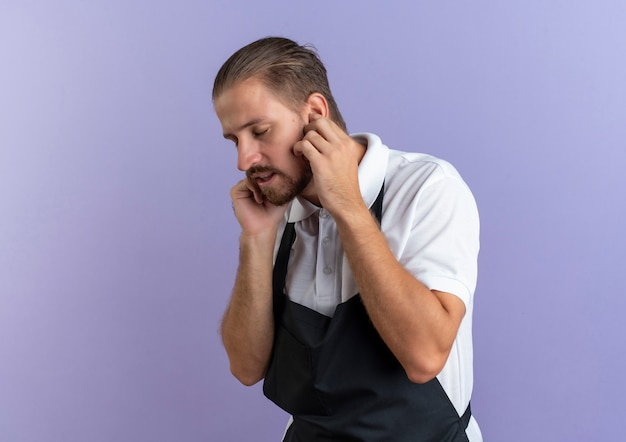 Unpleased young handsome barber wearing uniform putting fingers in ears with closed eyes isolated on purple background with copy space