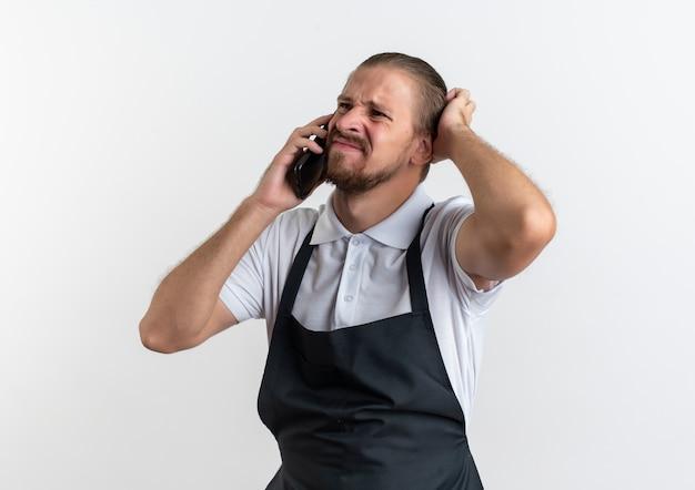 그의 머리를 만지고 흰색 배경에 고립 된 측면을보고 전화로 얘기하는 유니폼을 입고 불쾌한 젊은 잘 생긴 이발사