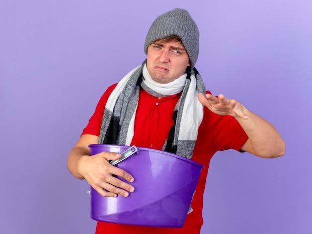冬の帽子とスカーフを身に着けている不機嫌な若いハンサムな金髪の病気の男は、コピースペースで紫色の壁に隔離された空気中に手を保つプラスチック製のバケツを保持しています