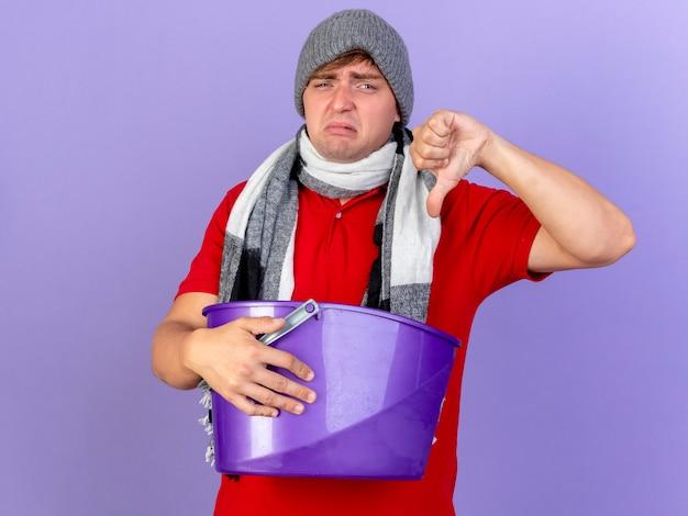 冬の帽子とスカーフを身に着けている不機嫌な若いハンサムな金髪の病気の男は、コピースペースで紫色の背景に分離された親指を下に示すカメラを見てプラスチック製のバケツを保持しています
