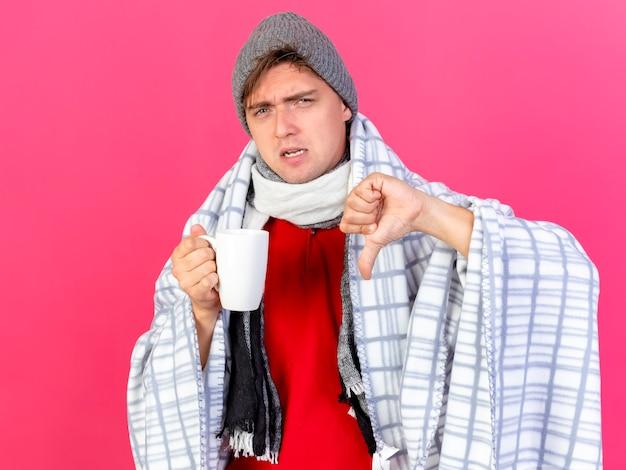 冬の帽子とスカーフを身に着けている不機嫌な若いハンサムな金髪の病気の男は、真っ赤な背景に分離された親指を下に表示しているカメラを見て格子縞の保持カップに包まれています