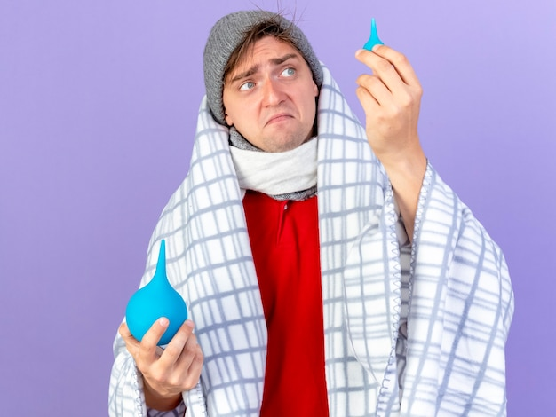 Недовольный молодой красивый блондин больной мужчина в зимней шапке и шарфе, завернутый в плед, держит клизмы, поднимает малыша и смотрит на него изолированно на фиолетовой стене
