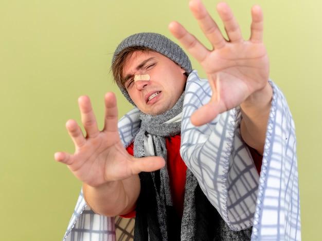 オリーブグリーンの背景に分離されたカメラを見てカメラに向かって手を伸ばして格子縞に包まれた冬の帽子とスカーフを身に着けている不機嫌な若いハンサムな金髪の病気の男