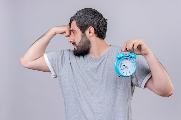 Unpleased young handsome caucasian man holding alarm clock looking at side and putting hand on forehead isolated on white background
