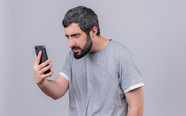 Giovane uomo caucasico bello dispiaciuto che tiene e che esamina telefono cellulare isolato su fondo bianco con lo spazio della copia
