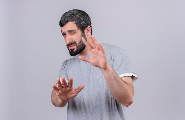 不機嫌そうな若いハンサムな白人男性がカメラに向かって手を伸ばして、コピースペースのある白い背景に孤立していないことを身振りで示す