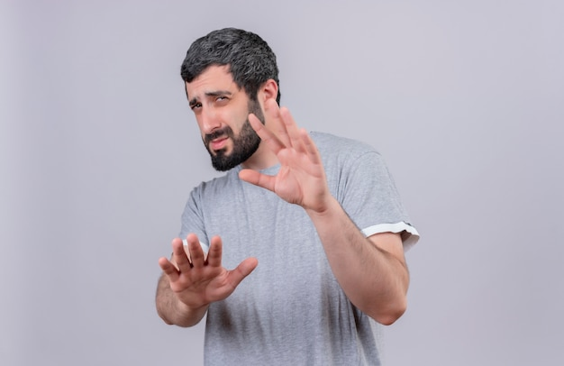 Giovane uomo caucasico bello dispiaciuto che allunga le sue mani verso la macchina fotografica che non gesturing isolato su fondo bianco con lo spazio della copia