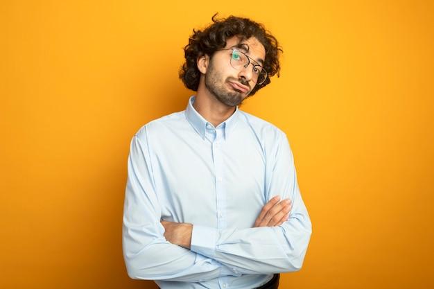 복사 공간 오렌지 배경에 고립 된 카메라를보고 닫힌 자세로 서 안경을 쓰고 불쾌한 젊은 잘 생긴 백인 남자