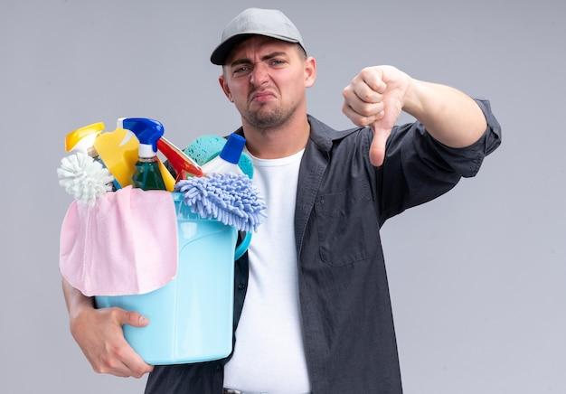 白い壁に隔離された親指を下に示すクリーニングツールのバケツを保持しているtシャツとキャップを身に着けている不機嫌な若いハンサムなクリーニング男