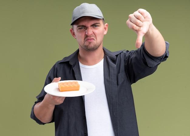 オリーブグリーンの壁に分離された親指を下に示すプレートにスポンジを保持しているtシャツとキャップを身に着けている不機嫌な若いハンサムな掃除人