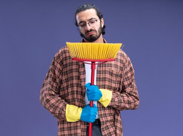 Недовольный молодой красивый уборщик в футболке и перчатках, держащий и смотрящий на швабру, изолированную на синей стене