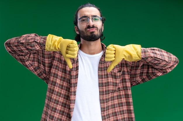 Недовольный молодой красивый уборщик в футболке и перчатках показывает палец вниз на зеленой стене