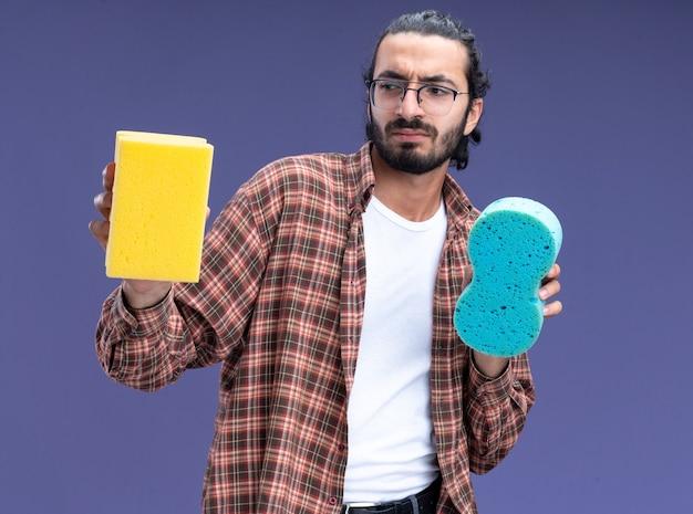 Insoddisfatto giovane bel ragazzo delle pulizie indossando t-shirt tenendo spugne isolate sulla parete blu