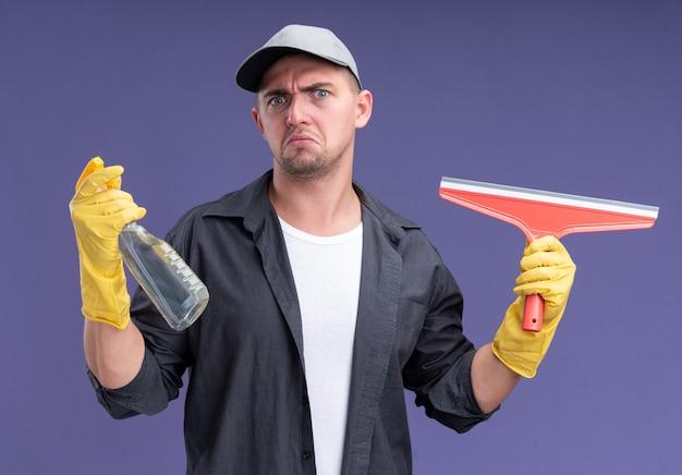 T-shirt da portare dispiaciuto giovane bello delle pulizie con cappuccio e guanti che tengono la testa del mop e la bottiglia dello spruzzo isolata sulla parete viola