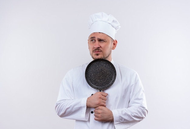 Unpleased young handsome cook in chef uniform holding frying pan looking at side isolated on white space