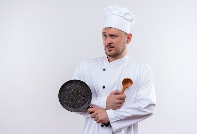 Giovane cuoco bello dispiaciuto in padella e cucchiaio della holding dell'uniforme del cuoco unico che esaminano lato isolato su spazio bianco