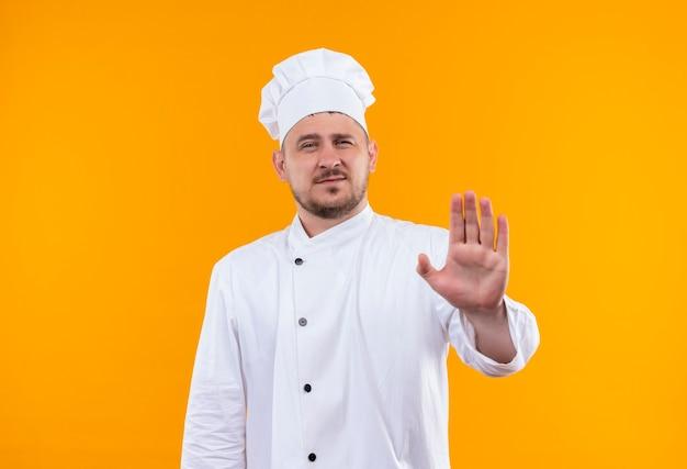 オレンジ色のスペースに隔離されたシェフの制服のジェスチャーストップで不機嫌な若いハンサムな料理人