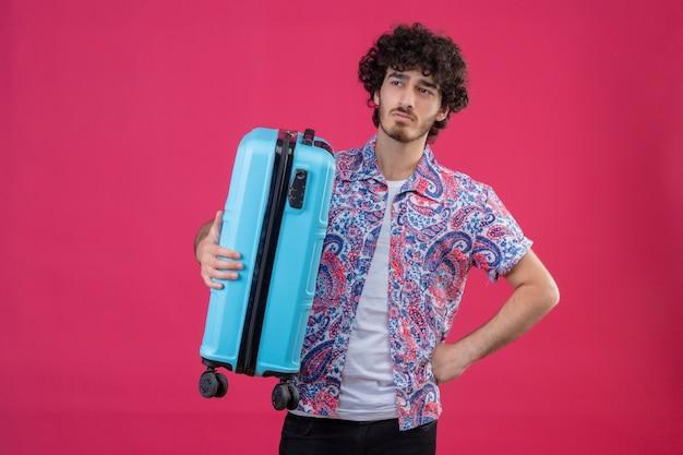 Uomo giovane bello riccio sgradevole del viaggiatore che tiene la valigia con la mano sulla vita sulla parete rosa isolata con lo spazio della copia