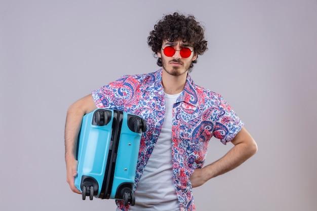 サングラスをかけ、孤立した白い壁に腰に手でスーツケースを保持している不機嫌な若いハンサムな巻き毛の旅行者の男