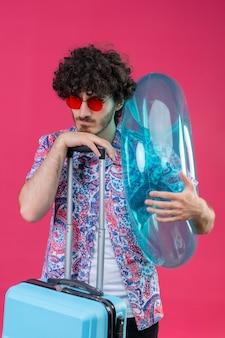 浮き輪を保持し、孤立した紫色の壁にスーツケースに手を置くサングラスを身に着けている不機嫌な若いハンサムな巻き毛の旅行者