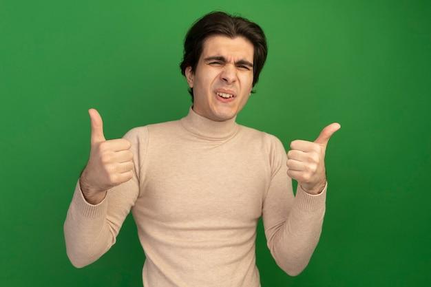 엄지 손가락을 보여주는 불쾌한 젊은 잘 생긴 남자는 녹색 벽에 고립