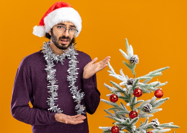 Unpleased young handsome guy standing nearby christmas tree wearing christmas hat with garland on neck points at tree isolated on orange wall