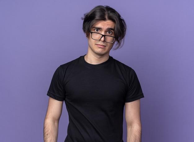 검은 티셔츠와 보라색 벽에 고립 된 안경을 쓰고 불쾌한 젊은 잘 생긴 남자