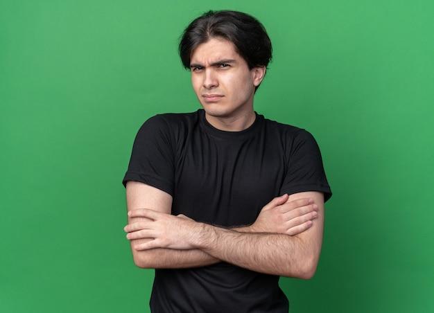 녹색 벽에 고립 된 검은 티셔츠 횡단 손을 입고 불쾌한 젊은 잘 생긴 남자