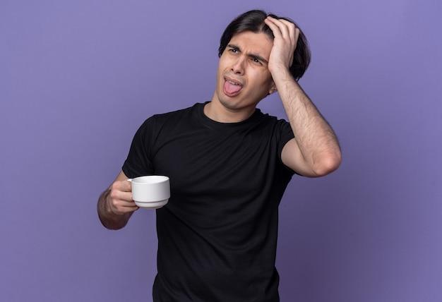 舌を示すコーヒーのカップを保持し、紫色の壁で隔離の頭に手を置く黒いtシャツを着て不機嫌な若いハンサムな男