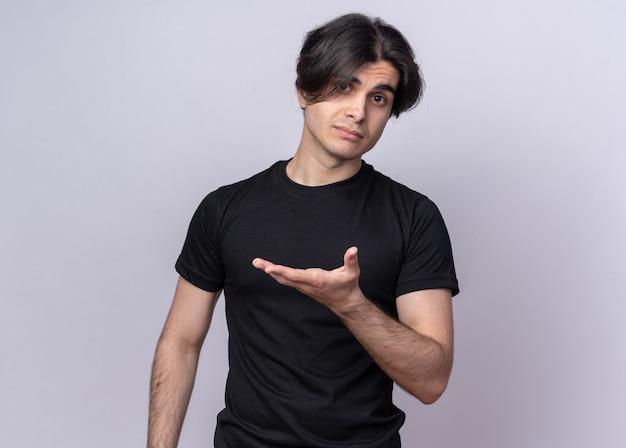흰 벽에 고립 된 측면에서 손으로 검은 티셔츠 포인트를 입고 불쾌한 젊은 잘 생긴 남자