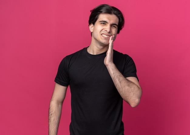 분홍색 벽에 고립 된 아픈 치아에 손을 넣어 검은 티셔츠를 입고 불쾌한 젊은 잘 생긴 남자