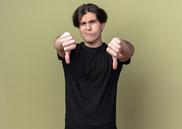 オリーブ グリーンの壁に孤立した親指を下に示す黒い t シャツを着た不愉快な若いハンサムな男