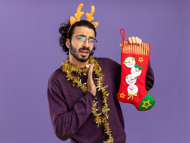 Unpleased young handsome guy wearing christmas hair hoop with garland on neck holding christmas socks holding out hand at socks isolated on blue background