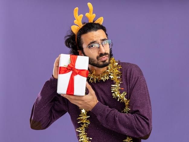 青い背景で隔離のギフトボックスを保持している首に花輪とクリスマスの髪のフープを身に着けている不機嫌な若いハンサムな男