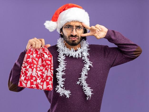 青い背景で隔離の平和のジェスチャーを示すクリスマスバッグを保持している首に花輪とクリスマス帽子をかぶって不機嫌な若いハンサムな男