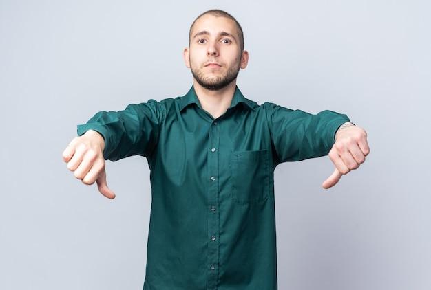 親指を下に見せて緑のシャツを着ている不機嫌な若いハンサムな男
