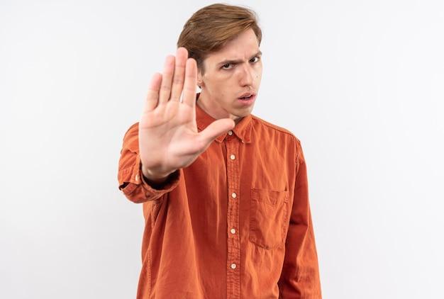 Un bel ragazzo scontento che indossa una camicia rossa che mostra il gesto di arresto