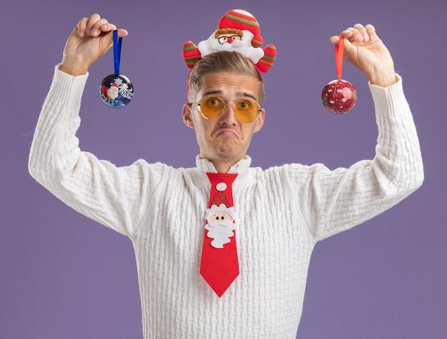 Giovane bel ragazzo dispiaciuto che indossa la fascia di babbo natale e cravatta con gli occhiali che alzano gli ornamenti della palla di natale che guarda l'obbiettivo isolato su fondo viola