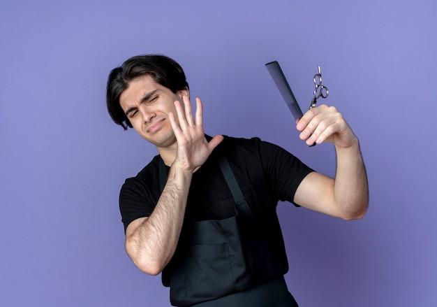 Barbiere maschio bello giovane insoddisfatto in tenuta uniforme e non guarderà le forbici e la pettinatura isolate sull'azzurro