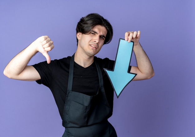 Unpleased young handsome male barber in uniform holding paper direction mark his thumb down isolated on blue