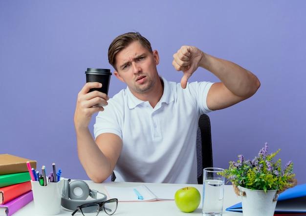 Giovane studente maschio bello dispiaciuto che si siede allo scrittorio con gli strumenti della scuola che tengono la tazza di caffè il suo pollice giù isolato sull'azzurro