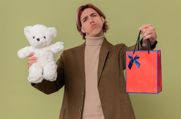 Unpleased young handsome man holding white teddy bear and gift bag