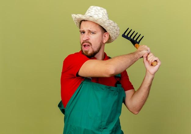 제복을 입은 불쾌한 젊은 잘 생긴 슬라브 정원사 및 복사 공간이 올리브 녹색 벽에 고립 된 갈퀴로 누군가를 칠 준비가 된 갈퀴를 들고 모자