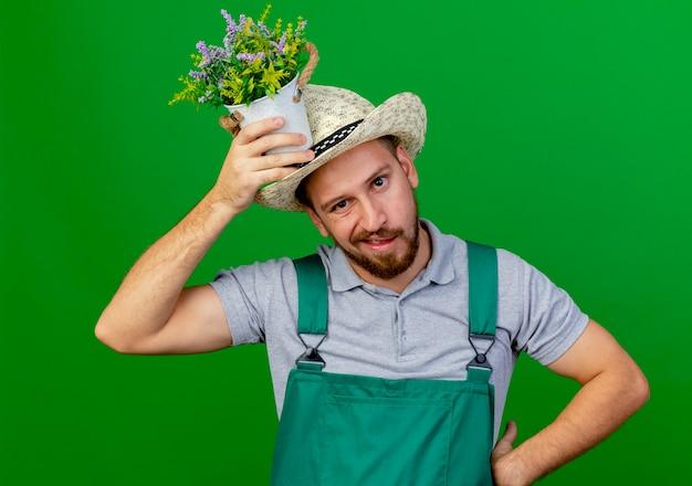 Giovane giardiniere slavo bello dispiaciuto in uniforme e cappello che tiene vaso di fiori sulla testa tenendo la mano sulla vita alla ricerca