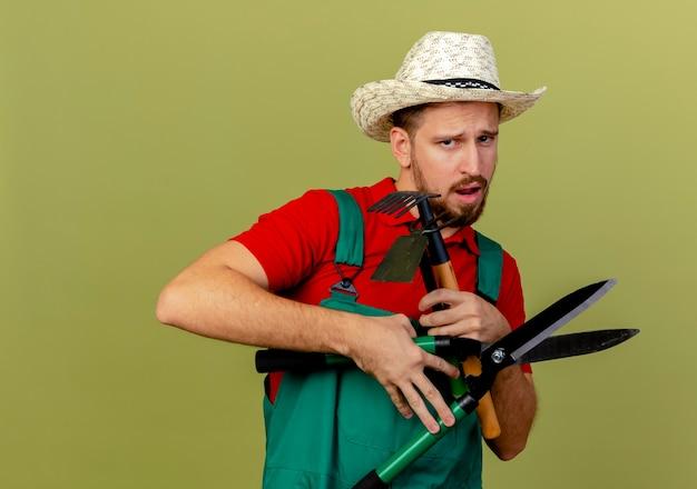 Giovane giardiniere slavo bello dispiaciuto in uniforme e cappello che tengono gli strumenti del giardiniere che sembrano isolati
