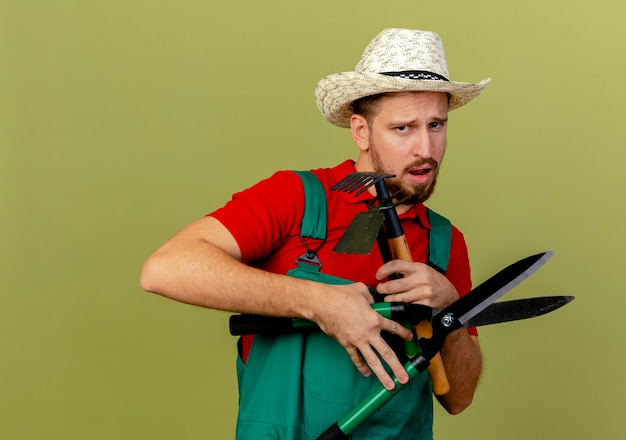 Unpleased young handsome slavic gardener in uniform and hat holding gardener tools looking isolated