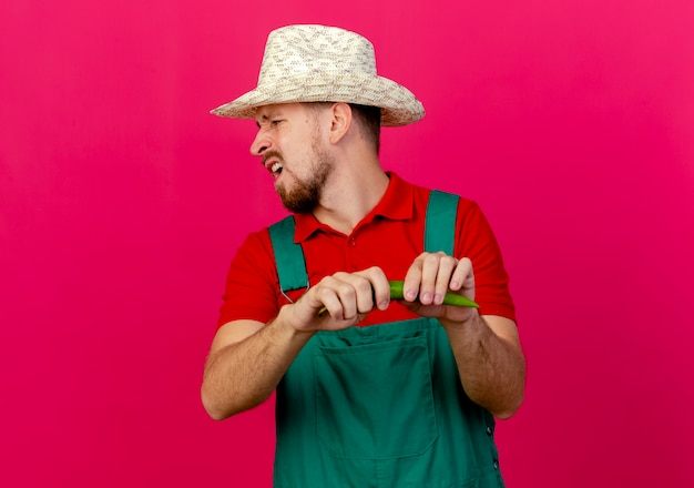 Unpleased young handsome slavic gardener in uniform and hat holding pepper turning head to side braking pepper Free Photo